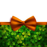 Saint Patricks Day vector background, realistic shamrock leaves and orange bow Royalty Free Stock Images