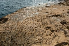 Carved and engraved names in the rock. SAINT PETER`S POOL, MALTA - AUGUST 21, 2017: People carving and engraving their names and initials in the rocks at Saint Stock Photography