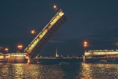 Saint Petersburg, bridging of bridge at night, drawbridge on Neva river at White nights. Russia Stock Photos