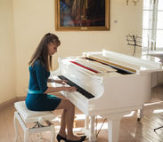 Saint-Petersburg. Female musician playing on a white grand piano. stock photo