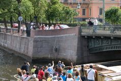 Saint-Petersburg. Russia. SAINT-PETERSBURG, RUSSIA - JULY 10, 2009: Tourists throw coins to a small bronze bird to have a good luck. The Chizhik-Pyzhik Statue Stock Photo