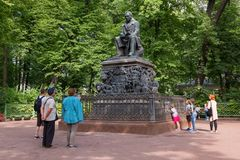 Tourists near the monument. SAINT PETERSBURG, RUSSIA - AUGUST 18, 2017: The monument to the fabulist Ivan Krylov. Summer garden. It was established in 1855 near Royalty Free Stock Photo