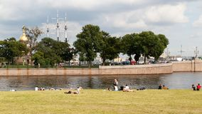 SAINT PETERSBURG, RUSSIA - AUGUST 18, 2017: People resting on the banks of the Neva river at the Peter-Paul fortress. SAINT PETERSBURG, RUSSIA - AUGUST 18, 2017 royalty free stock photo
