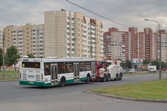 Saint Petersburg, Russia - August 16, 2018: Repair and recovery vehicle towing a broken city bus. stock photo