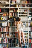 Woman reaches for book on shelf in bookstore royalty free stock image