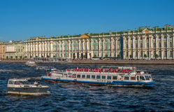 Saint Petersburg, Russia - July 30, 2017: Hermitage palace on the bank of Neva river. The waterfront is moored excursion Royalty Free Stock Photography
