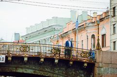 People stand on a bridge over a canal in St. Petersburg stock photos