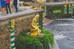 Saint Petersburg, Russia - June , 2016- Peterhof. fountain girl sitting on the stone, the tale of the mermaid. SAINT PETERSBURG, RUSSIA - June , 2016: tourists Stock Photography