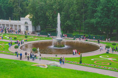 Saint Petersburg, Russia - June , 2016- Peterhof. round fountain with one jet and green slope Royalty Free Stock Images