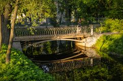 A bridge in Tavrichesky garden. Saint Petersburg, Russia. May 23, 2018. A bridge lit with sunset beams in Tavrichesky garden stock images