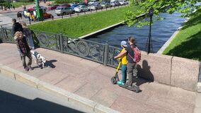 Dad and son ride the same electric scooter together. Walk through the most beautiful city in Russia.