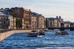 SAINT-PETERSBURG, RUSSIA - MAY,09 2014: Fontanka river with tourist boats full of people. Telephoto shot at daylight.  stock photo