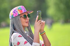 SAINT PETERSBURG, RUSSIA - MAY 19, 2019: Neivest girl with dreadlocks wearing glasses and a baseball cap shoots on a smartphone, a. SAINT PETERSBURG, RUSSIA stock photos