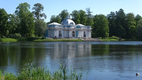 Pavilion `Grotto` on a Large pond on a Sunny may day. Catherine Park of Tsarskoye Selo, St. Petersburg. SAINT PETERSBURG, RUSSIA - MAY 29, 2018: Pavilion `Grotto stock footage