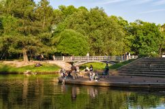 A warm evening by the pond in Tavrichesky garden. Saint Petersburg, Russia. May 23, 2018. People having rest by the pond in Tavrichesky garden stock photos