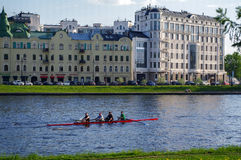Saint Petersburg, Russia - May 21, 2014: tree people in a kayak on the Fontanka river, sunny day Royalty Free Stock Photos