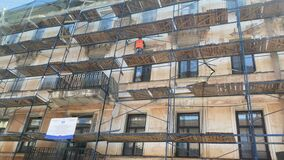 A worker in an orange vest repairs the facade of an old building while standing on a scaffold.
