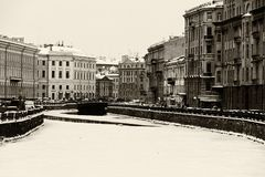St. Petersburg Moika river embankment. Saint Petersburg, Russia: the Moika river embankment by a winter day covered by ice and snow with old architecture Stock Photo