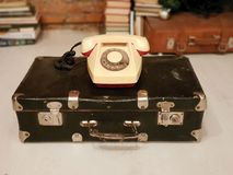 SAINT-PETERSBURG, RUSSIA:Old Soviet suitcase and a beige rotary phone at January 30, 2019 royalty free stock photo