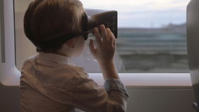 In Saint-Petersburg, Russia in train rides a little boy with virtual reality glasses. Travel and entertainment stock video