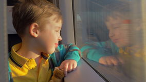 In Saint-Petersburg, Russia in train rides a little boy who looks out the window and holding a toy. Outside window seen railroad and buildings stock video