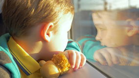 In Saint-Petersburg, Russia in train rides a little boy who looks out the window and holding a toy. Outside window seen railroad, people and buildings stock footage