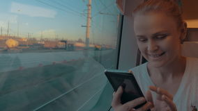 In Saint-Petersburg, Russia in train rides young girl and looking out the window, holding a cell phone. And working on it. Outside window seen railroad and stock video