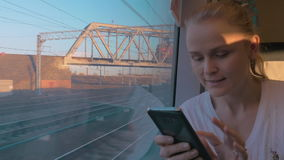 In Saint-Petersburg, Russia in train rides young girl and looking out the window. Holding a cell phone and working on it. Work and travel stock footage