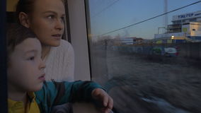 In Saint-Petersburg, Russia in train rides a young mother with a son and looking out the window. Outside seen railroad and buildings stock video