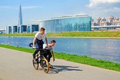 Saint-Petersburg. RUSSIA. 05.18.2018. Two boys ride a bike and skateboard. stock image