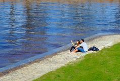 A beautiful couple guy with a girl sitting by the water taking a selfie. stock photo