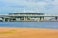 Saint Petersburg stadium Zenith football stadium on the Krestovsky Island behind the bridge and the gulf. Royalty Free Stock Photo