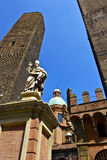 Saint Petronius Statue near Two Towers in Bologna. Saint Petronius Statue in Bologna pictured with high perspective with Two Towers and blue sky on the stock photos