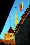 Saint Pierre Cathedral Geneva dans la vieille ville avec le Suisse et les drapeaux de Genève Photographie stock libre de droits