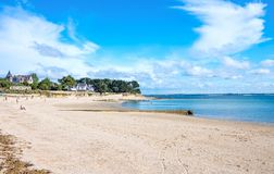 Landscapes and architectures of Brittany. Saint Pierre Quiberon, France - August 9, 2017: View of the great beach of the village, with people walking and Royalty Free Stock Photography