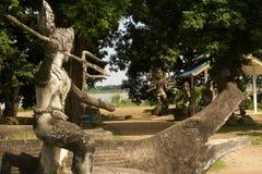 Saint prepares to slay a crocodile with trident. A saintly figure prepares to slay a mean looking crocodile with his trident, at Buddha Park, near Vientiane Royalty Free Stock Photos