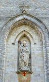 Saint Servatius church in Wemmel, Belgium. Statue of the saint on entry to Saint Servatius or Sint Servaas church in Wemmel, Belgium with attributes of the city Stock Photos