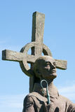 A saint statue holding a staff with a cross and blue sky backgro. A saint statue holding a staff on Holy island, England, with a cross behind them. The backdrop Stock Image