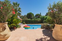 Saint Tropez, Cote-dAzur France 28-7-2017 View between 2 plants baking on a Mediterranean garden with swimming pool and bright blu stock image