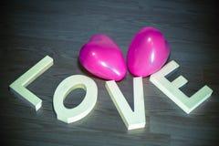 Saint Valentin actuel - aimez avec le fond en bois de ballons roses de coeur Photographie stock libre de droits