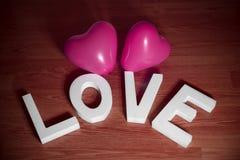 Saint Valentin actuel - aimez avec le fond rose de rouge de ballons de coeur Photographie stock libre de droits