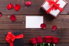 Saint-Valentin : Carte de papier vide blanche, roses rouges, anneau d'or et cadeau de boîte avec le ruban Photo libre de droits