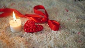 Saint Valentin de décoration avec la combustion de bougie et ruban sur le sable banque de vidéos