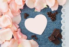 Saint-Valentin, fond bleu de denim avec le pétale de rose rose mou Images stock