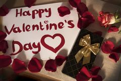 Saint-Valentin heureuse écrite dans le rouge à lèvres rouge autour des pétales de rose rouges et d'une rose photo stock