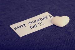 Saint-Valentin heureuse manuscrite sur une carte avec un coeur blanc Photographie stock