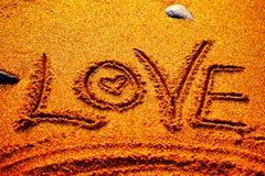 Saint Valentin heureux - aimez écrit sur la plage Photos stock