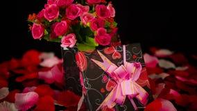 Saint Valentin heureux avec le bouquet de fleur de décoration, les boîte-cadeau et la longueur de pétales de rose banque de vidéos
