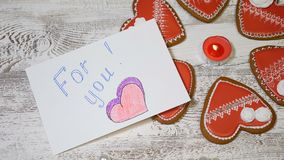 Saint. Valentine`s Day background. Heart shaped ginger biscuits,burning tea candle on wooden background. hand drops For. Saint. Valentine s Day background. Heart stock footage