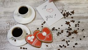 Saint Valentine`s Day concept. Coffee in white cups, home made heart shaped ginger biscuit on wooden background. hand. Saint Valentine s Day concept. Coffee in stock video